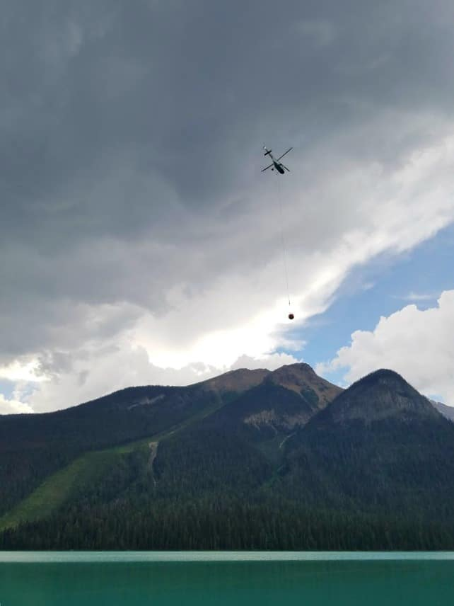Helicopter over Emerald Lake picking up water to put out a small brush fire - BC Canada Yoho National Park