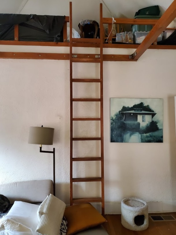 A step ladder leading up to a storage area in old home